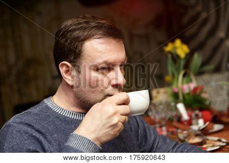 Man has tea in a dark cafe