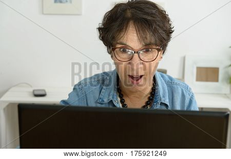 beautiful mature woman with eyeglasses websurfing on laptop