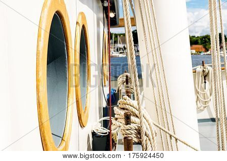 Coiled rope lines stored on belaying pins on a sailing vessel