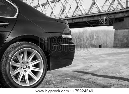 Senta, Serbia: March 4th, 2017. Close-up of beautiful black BMW 750Li car, photographed outdoor on a dock in Senta, besides beautiful big iron bridge.