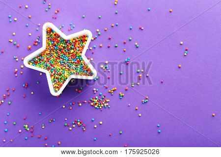 Colorful sprinkles on a purple background, close up
