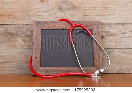Blank Blackboard And Stethoscope On Wooden Background