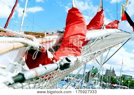 Details of bowsprit and gathered red sail of the tall ship on the cloudy sky background. Concepts: prosperity, optimism, positive, future