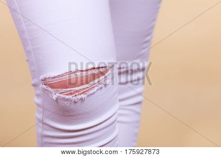 Fashion and current trends concept. Detailed closeup of white woman trousers with holes on knees
