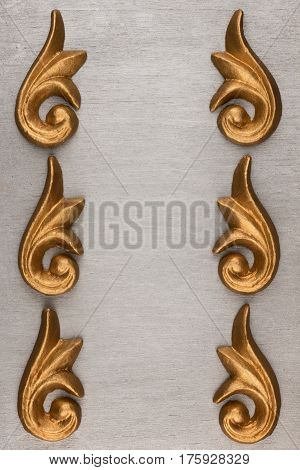 Luxury frame made of golden stucco plaster lying on silver surface with space for your text