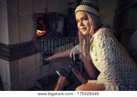 Young blonde woman spliting logs and burning wood in stove at home