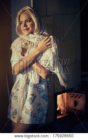 Young blonde beautiful woman in kerchief basking near heating stove at own home