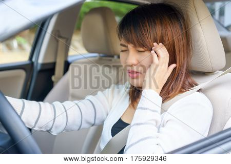 Closeup portrait of young woman touching her temple feels headache in her car after driving car for long time