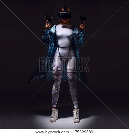 Young blonde woman gaming virtual reality with head mounted display and joysticks in white clothes and turquoise cloak