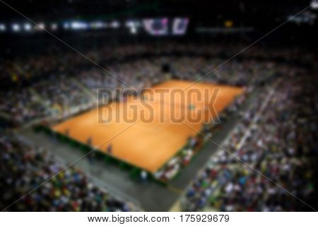blurred background of clay tennis court inside sports arena and audience watching the game