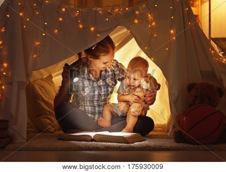 reading and family games in children's tent. mother and child daughter with book and flashlight before going to bed