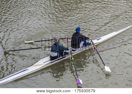 Two people training in a canoe on a river. Two seater kayak.