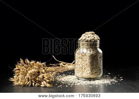 Oat bunch and flakes in flavouring jar isolated on black background. Grain bouquet golden oats spikelets on dark wooden table can filled with dried grains. Food bakery concept