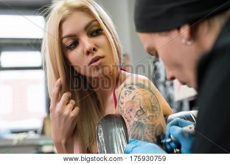 Sexy blonde posing in tattoo studio while a master drawing tattoo on her forearm