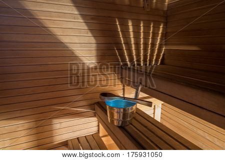 Wellness and spa conception. Sauna bath bucket with blue water, scoop, striped light, wooden walls and timber bench