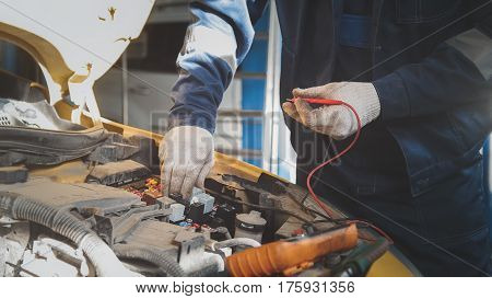 Mechanic works car electrics with voltmeter - electrical wiring, close up