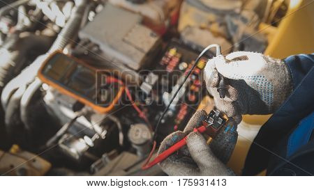 Mechanic works with car electrics - electrical wiring, voltmeter, close up