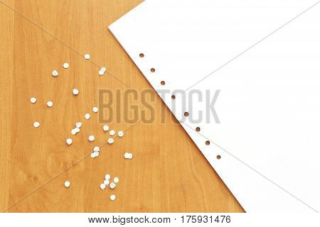 Paper with holes of hole puncher on wooden table. Punched paper list and confetti in office. Bright office background.
