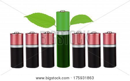 Six batteries in red color, AAA type, one battery is green, with green leaves on a white background isolated