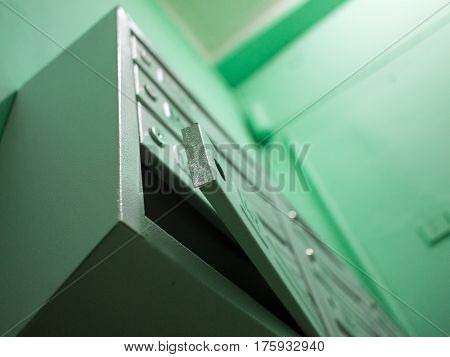 Open gray mailbox without lock in the entrance with green walls a fluorescent lamp