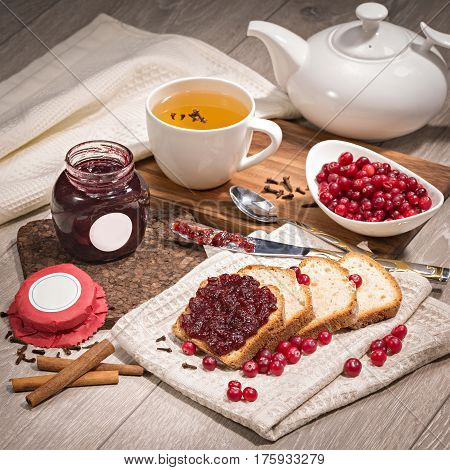 Lingonberry jam on bread on wooden background