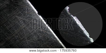 Razor blade by microscope. Microscopic scratched steel surface