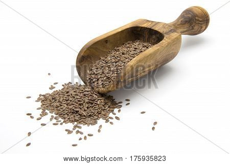 Flaxseeds in wooden scoop on white isolated background