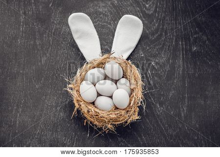 A Nest With Three White Easter Eggs And Bunny Ears At Home On Easter Day. Celebrating Easter At Spri