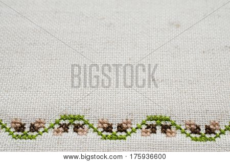Handmade Embroidery by Cross Stitch in the View of Acorns. Texture of Beige Natural Linen Fabric with Embroidery for Background. Selective Focus.