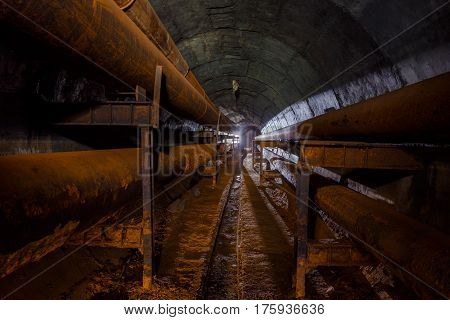 Rusty pipes of the pipeline of the heating main in round technical tunnel