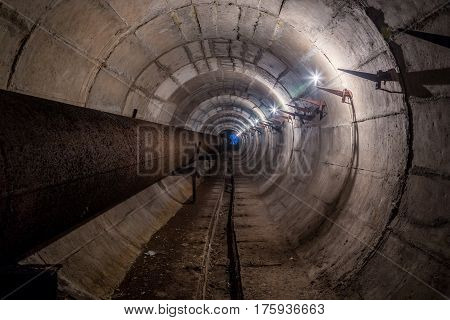 Old round dirty underground technical tunnel of heating duct with rusty pipeline