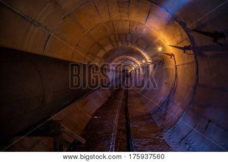 Round underground technical tunnel of heating main with rusty pipeline