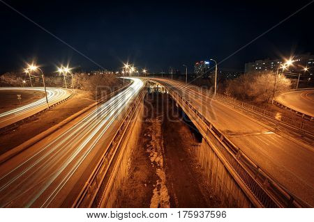 Light trails at night on the road with overpass. Voronezh