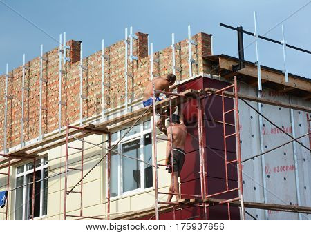 KIEV UKRAINE - March 14 2017: Construction workers insulating house facade with mineral rock wool. External wall insulation system (or EWIS) for energy saving.
