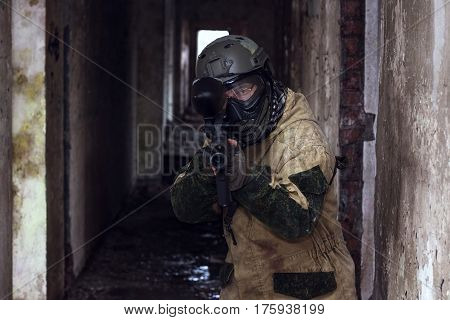 Shot of militaty man takes aim in lense with paintball weapon
