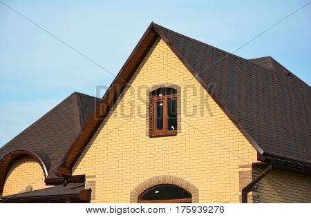 Asphalt Shingles Roofing Advantages. Roofing Construction House Building with Asphalt Shingles and Different Types of Roof Design.
