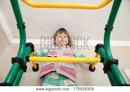 Children home workout. Little girl on gymnastic bar. Child health care and physical development concept. Happy and healthy childhood. Kid on horizontal bar. Toddler screw up eyes being afriad of height.