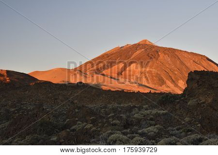 Top of Teide Volcano in the morning lite with some vegetation in shadow in foreground picture from Tenerife Spain.