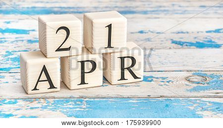 April 21st. Wooden cubes with date of 21 April on old blue wooden background.