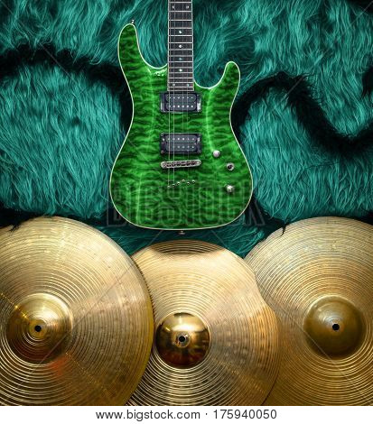 Green electric guitar with three cymbals on turquoise color faux fur wall. Musical instruments background