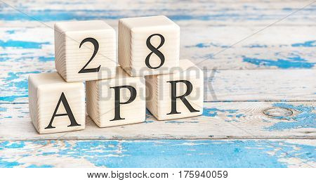 April 28th. Wooden cubes with date of 28 April on old blue wooden background.