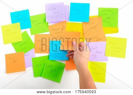 To do list - multicolored task notes with hadnd choosing one on white background