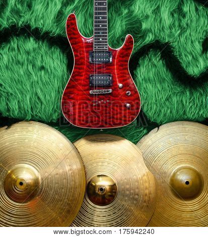 Red Electric guitar with three cymbals on green faux fur wall. Musical instruments background