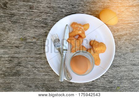 Fried Bread Stick Or Patongko And Soft-boiled Egg In White Dish With Fork And Knife On Wooden Backgr