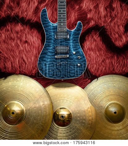 Blue electric guitar with three cymbals on faux fur wall. Musical instruments background