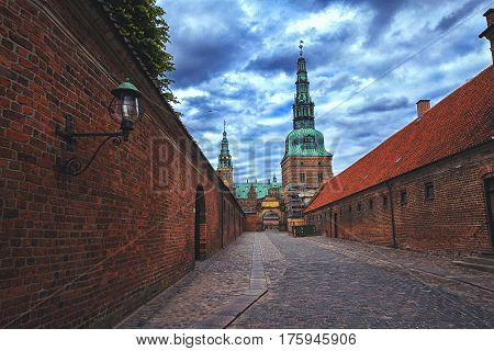 Entrance to Frederiksborg palace Denmark. Red brick fortress wall and green copper spiels of towers of renaissance castle Frederiksborg.