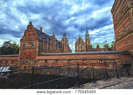 View of Frederiksborg palace Denmark from the bridge. Red brick fortress wall archway and green copper spiels of towers of renaissance castle Frederiksborg.