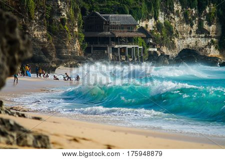 Ocean wave covering the people on balinese Dreamland beach