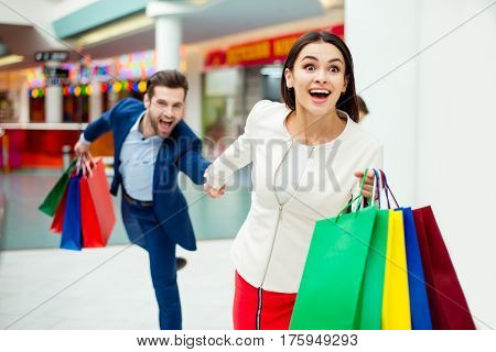 Hurry Faster! It's Shopping Time And Fun. Handsome Cheerful  Successful Happy  Man  Holding Hands An