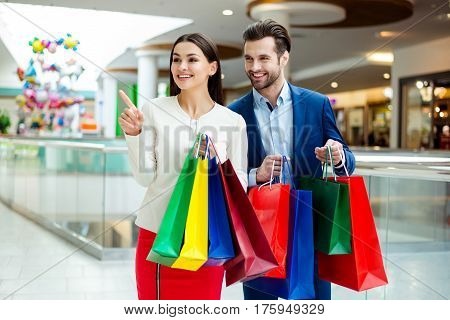 Cute Cheerful  Successful Happy Lovely Couple In Jacket Holding Colored Shopping Packages, Pointing